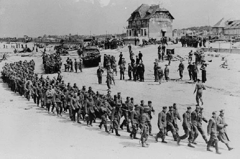 This image shows people in uniforms marching, there are other people standing in groups.