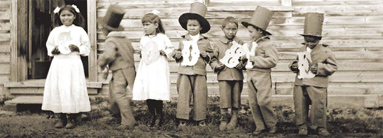 "Seven young childrean in ""finest dress"" costumes, holding letter that spell goodbye."