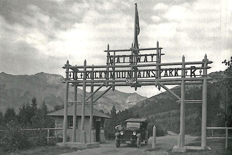 Mountains in the background, in the foreground a large wooden gate, a booth, and a man leaning against his old car posing for the photo.