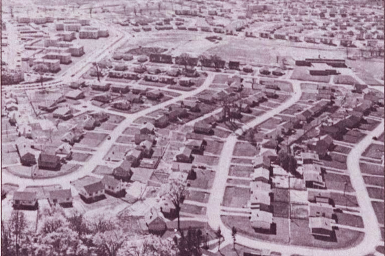 A gray-scale image of a suburban neighbourhood showing similar looking houses side-by-side.