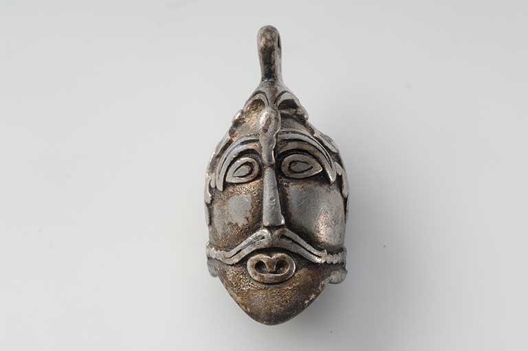 This image shows a silver pendant in the shape of a male head.