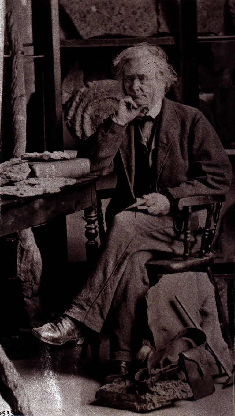 A man sits in a chair beside a table