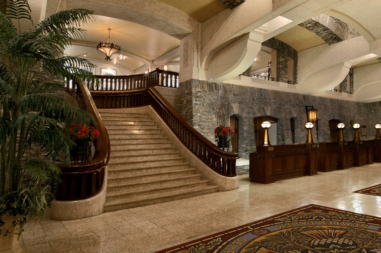 Photograph of the grande marble staircase at the Fairmont Banff Springs Hotel. Light marble, dark brown wooden banisters.