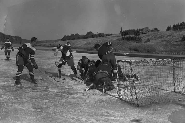This image shows men playing hockey on a frozen river in front of a net.