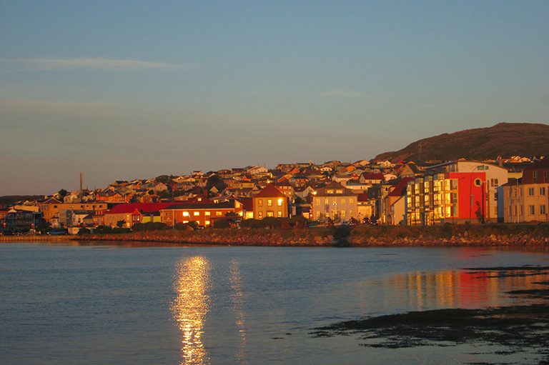 This image shows water in the front and houses on the shoreline glowing in a sunrise.